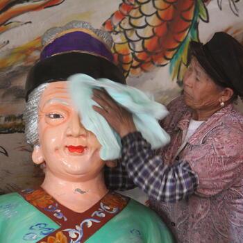 A woman scrubs the face of a Bai ancestor