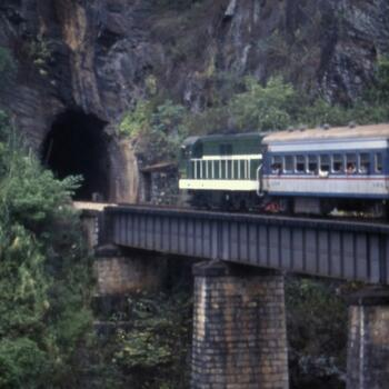 An old passenger train heads toward a tunnel on the Kunming Haiphong Railway